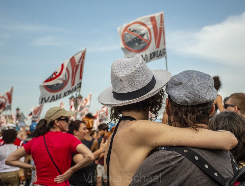 Two lovers hugging in front of protesters against cruise ships in Venice
